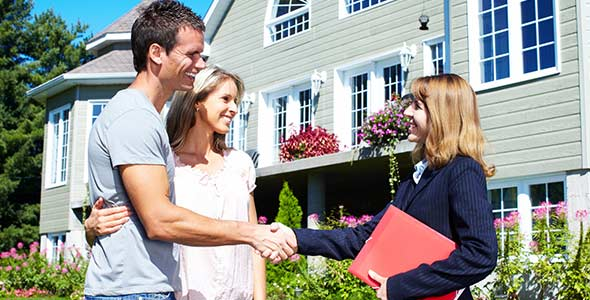 A Real Estate Agent shaking hands with new home owners