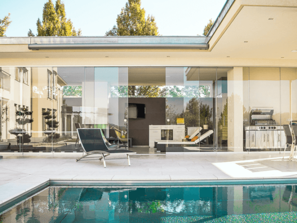 Modern pool home glass walls to the outdoor patio
